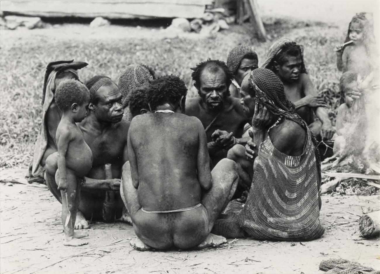 BD/326/26 - Ekagi-mannen beraadslagen onder elkaar, op de achtergrond bereiden vrouwen een varken